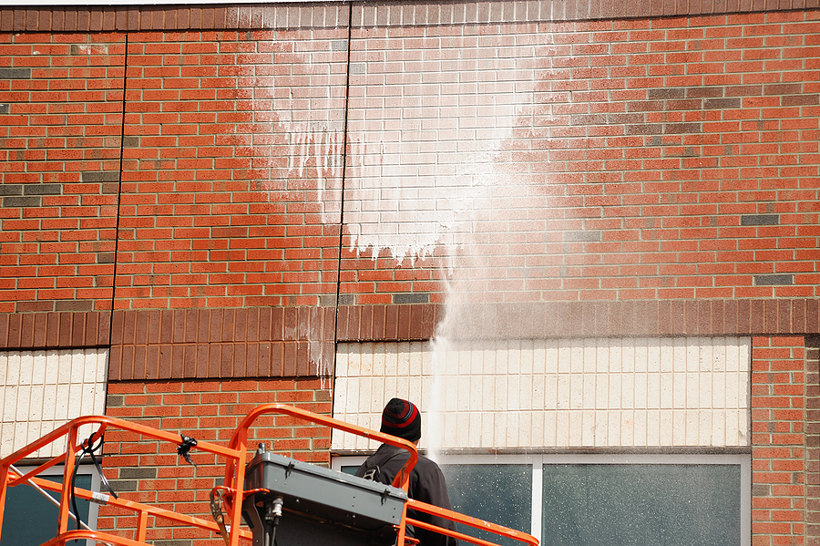man power washing the commercial brick wall