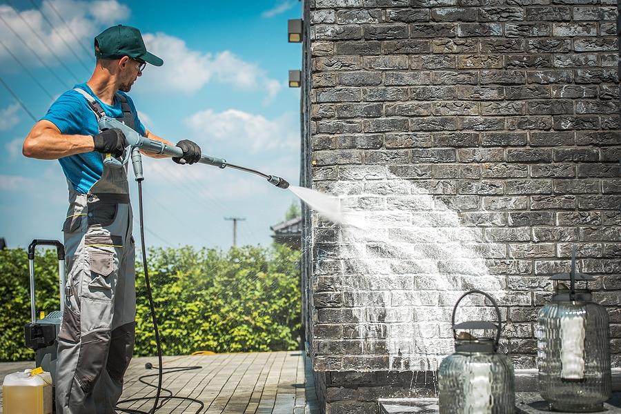 man power washing the brick wall