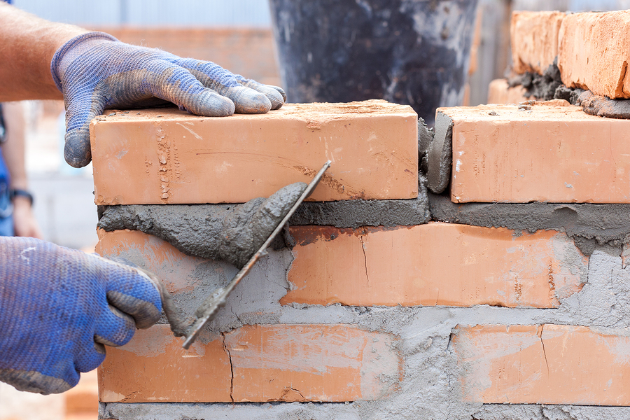 man putting cement and bricks