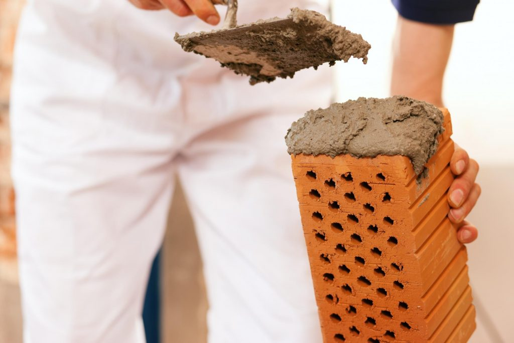 man putting cement on the brick